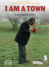 The film poster for 'I Am A Town' featuring a person in a suit smelling potted flowers while standing in a cemetery