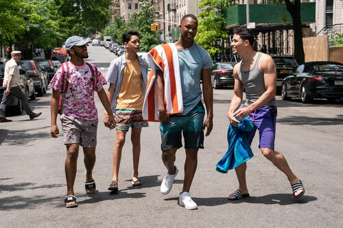 An image from the movie 'In The Heights' of four characters walking and talking on a street
