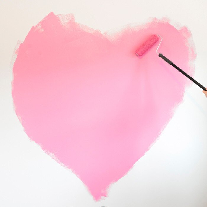 Someone painting a pink heart onto a white wall with a paint roller