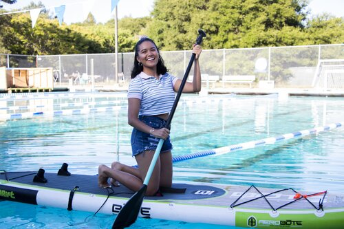 Student paddle boarding in the pool