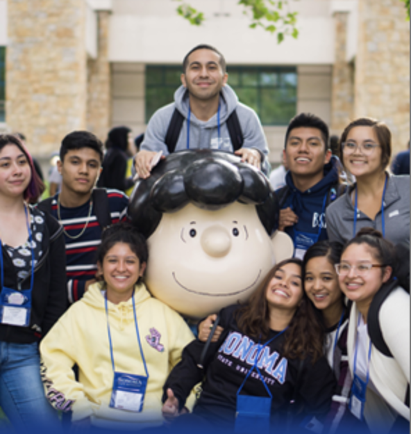 A group of students wearing name tags smiling and posing around the Lucy statue