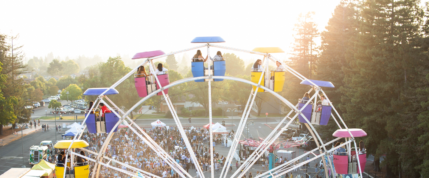 People on a multi-colored ferris wheel with a crowd, trees, and the sunset in the background