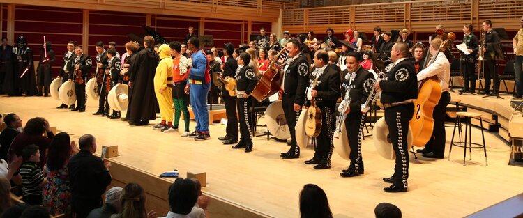 Musicians standing in a line on the indoor GMC stage