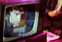 An image of a person's face on a television screen in a dimly lit room