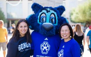 Judy K. Sakaki and Lobo greet new student to campus