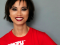 A portrait of Amazin LeThi smiling in a red t-shirt in front of a grey background