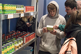 Two students stand next to shelves of canned goods, while inspecting a package