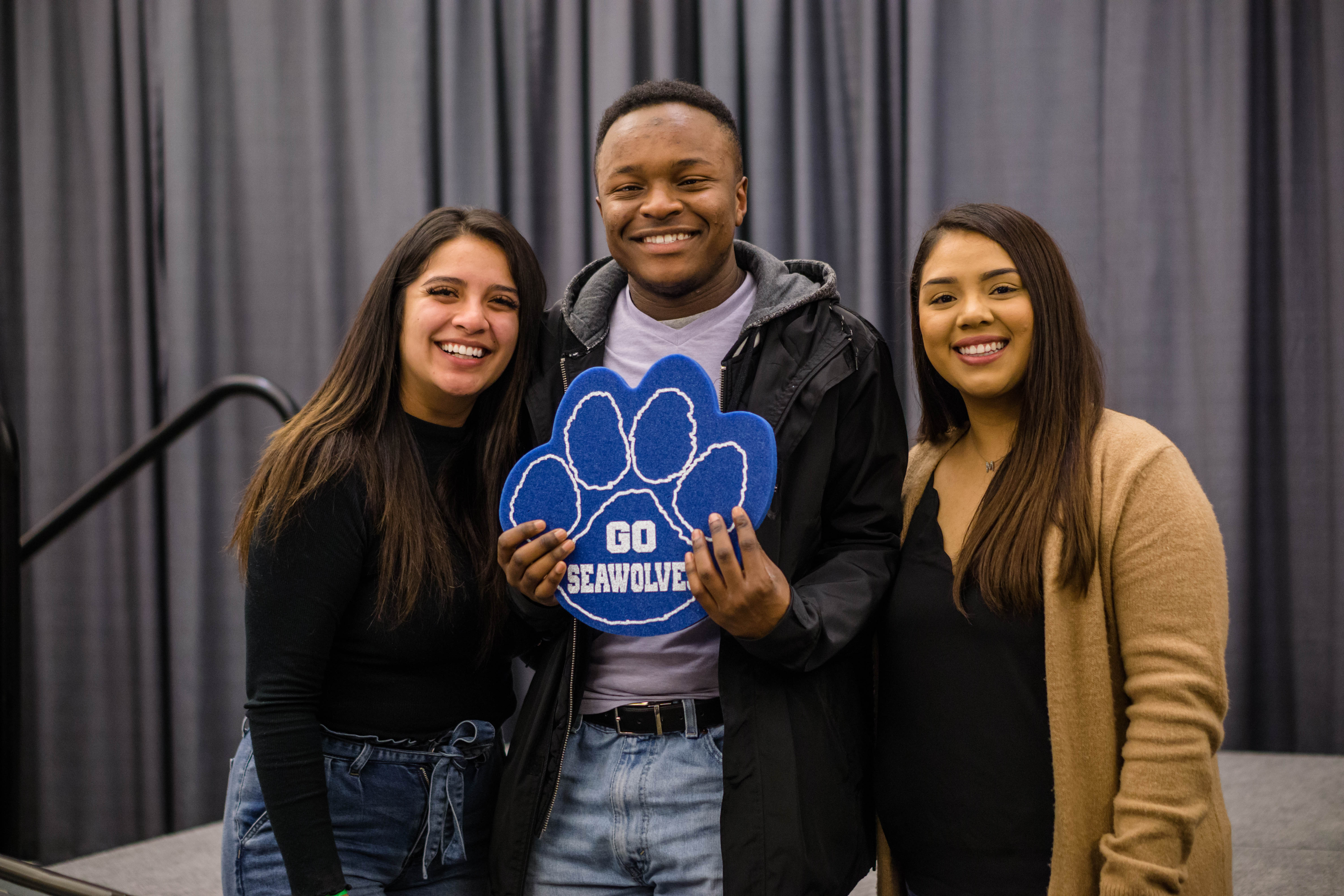 "3 students smile at the camera. The man in the middle holds a blue foam Seawolf paw that reads ""Go Seawolfs"""