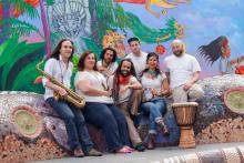 The seven members of Lior Ben Hur smiling and posing with their instruments in front of a colorful mural