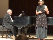 A person singing and a person playing piano on stage at the Vocal Repertory Recital