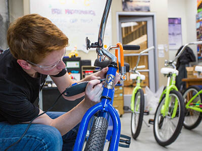 A person with red hair and safety glasses on using an electric tool on a blue bicycle