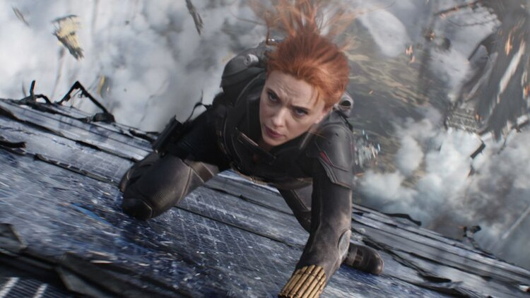 A screen capture from the film 'Black Widow' featuring the character Black Widow in the foreground with an explosion in the background