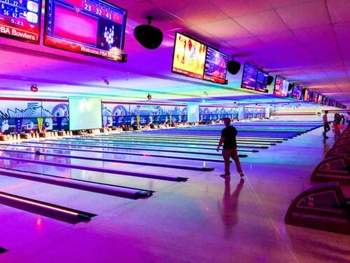 Someone bowling in a neon-illuminated bowling alley