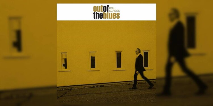The album cover of Boz Skaggs 'Out of the Blues' featuring a yellow tinted photograph of Boz walking in front of a building
