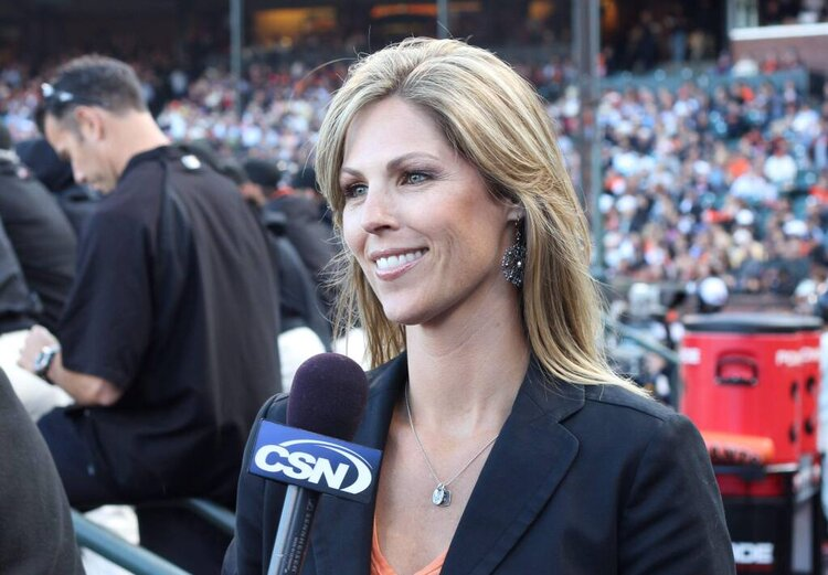 Woman with long brunette hair wearing black blazer speaks into a CSN microphone with large crows of people in stadium in the background
