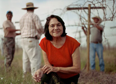 Delores Huerta smiling while kneeling in a field with three people in the background