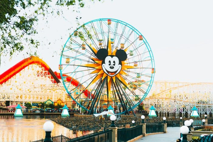 Disney outdoor theme park featuring a ferris wheel with Mickey Mouse's face on it