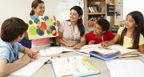 A young student showing their colorful artwork to a group of other smiling students and a teacher