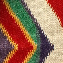 Knitted fabric with white, red, purple, green, and gold details