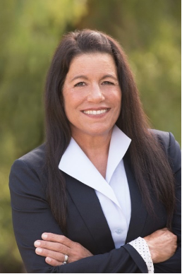 Portrait of Dr. Camille Filardo-Kraft smiling while wearing a black blazer above a white collared shirt in front of a blurred outdoor background
