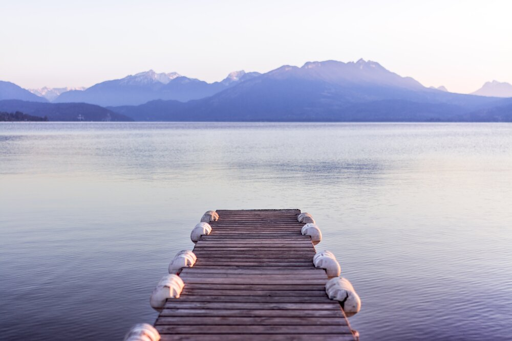 A dock leading into the flat water of a lake with hazy mountains in the background