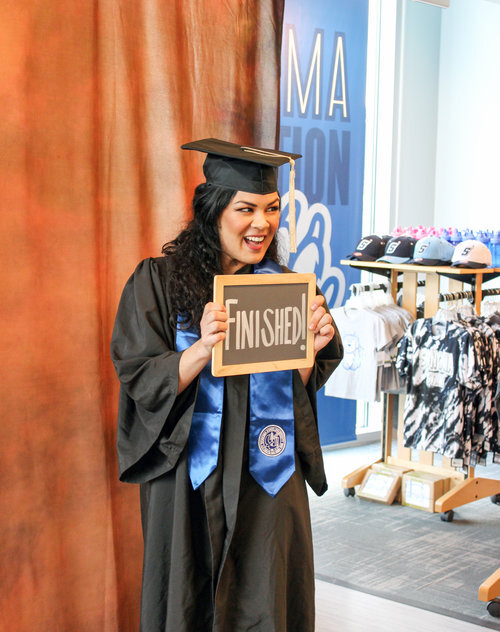 """A graduate with long black hair in Sonoma State University regalia smiling and holding a chalkboard with the word """"Finished!"""" on it"""