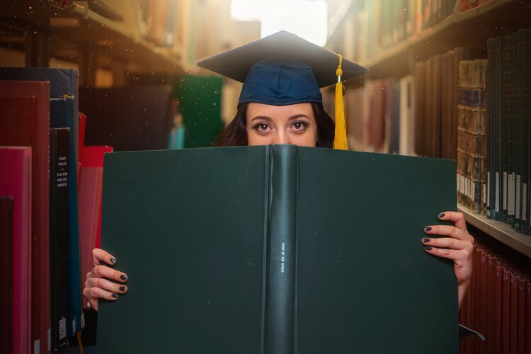Person inside a library holding a large green diploma in front of their face while wearing a blue graduate cap with a yellow tassel