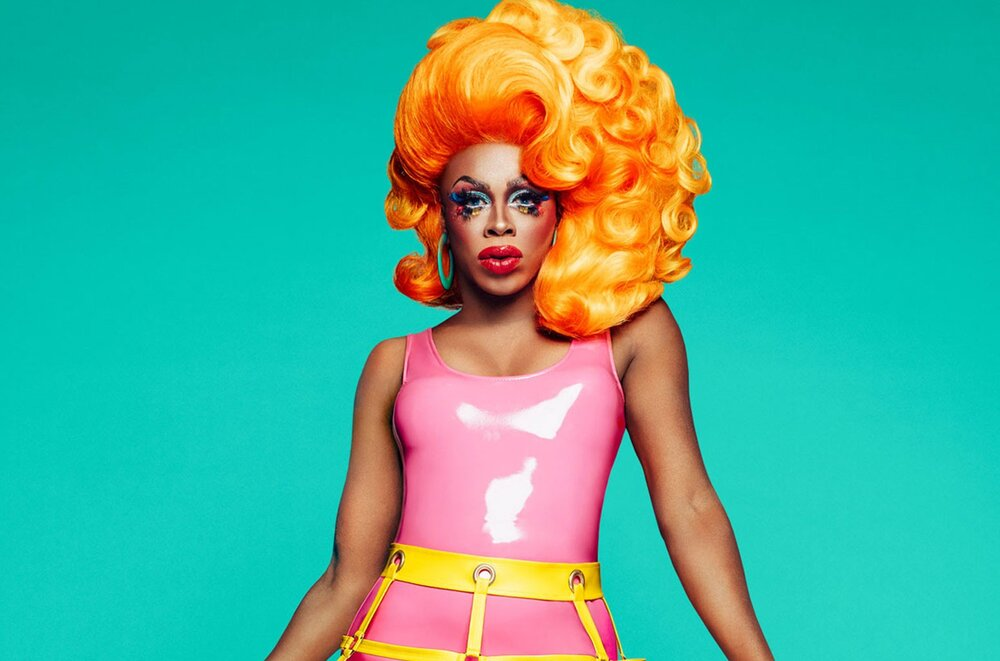 Portrait of Honey Davenport with orange hair, colorful makeup, and a pink latex dress on in front of a teal background
