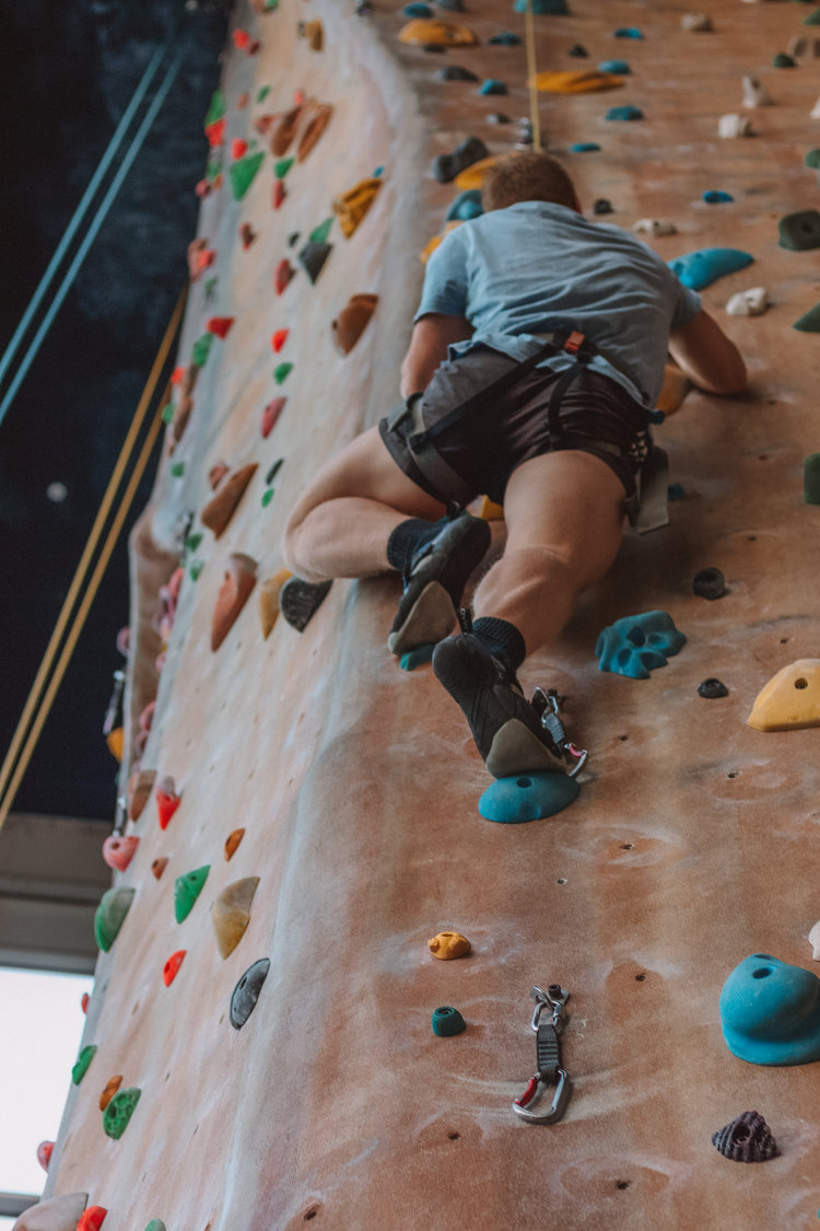 Person climbing indoor rock wall in blue t-shirt and grey shorts