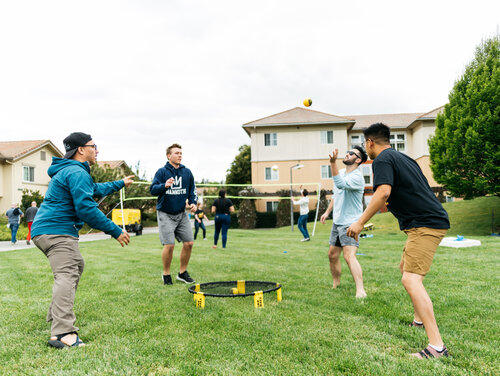 A group of 4 students playing spikeball on a lawn in residential housing