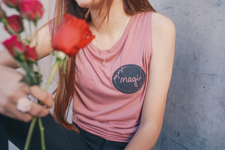 """A person with long red hair wearing a pink shirt with the words """"Magic"""" on it holding a small bouquet of colorful flowers"""
