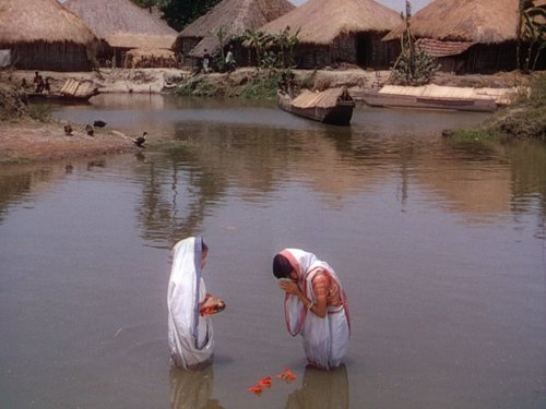 Two people praying in a river