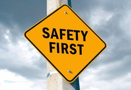A yellow diamond-shaped sign with the words 'Safety First' on it