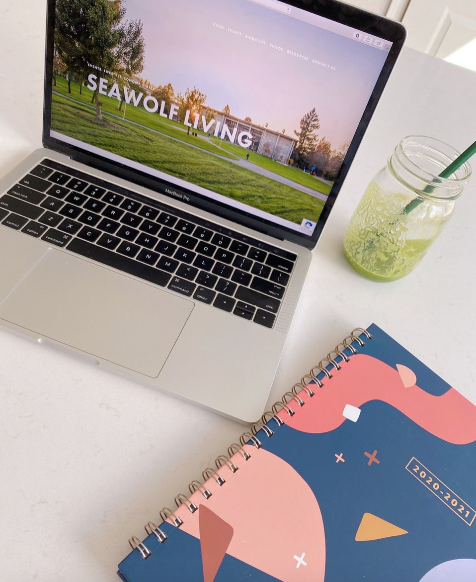 """A colorful planner, a green iced drink in a glass jar with a green straw, and an open laptop with the words """"Seawolf Living"""" on the screen"""