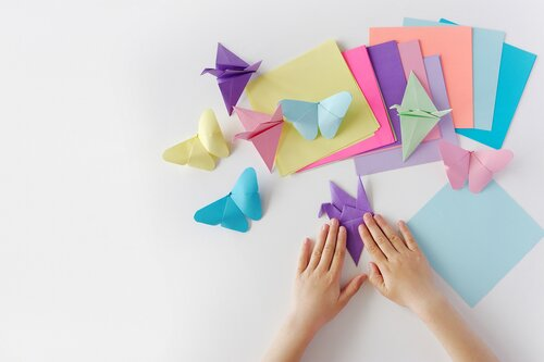 Someone folding multicolored origami butterflies