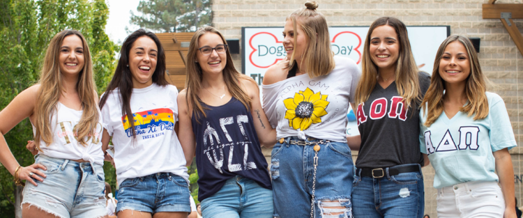 A line of six sorority members smiling and posing in the Student Center Plaza