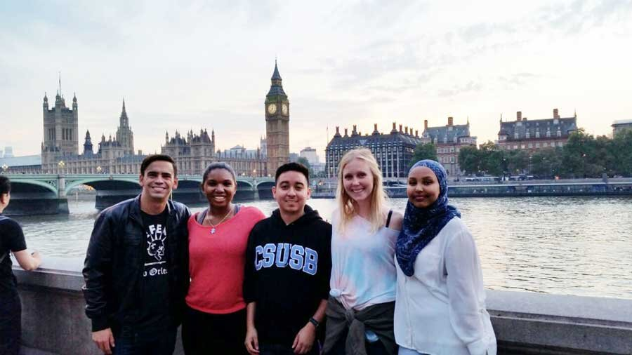 Five students smiling and posing in front of a European skyline featuring ornate buildings and a body of water