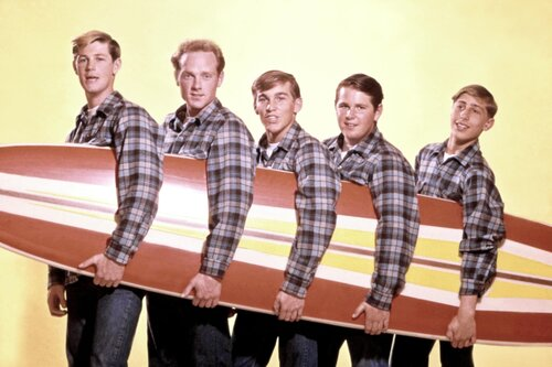 The five band members of The Beach Boys in a line wearing matching flannels while holding a singular surfboard