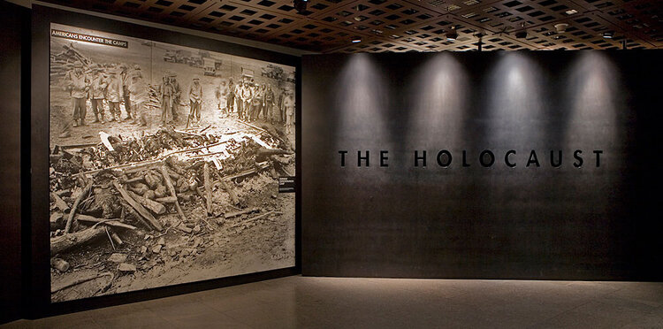 """Low-lit area of the U.S. Holocaust Memorial Museum featuring a large photograph and the words """"The Holocaust"""" under artistic lighting"""