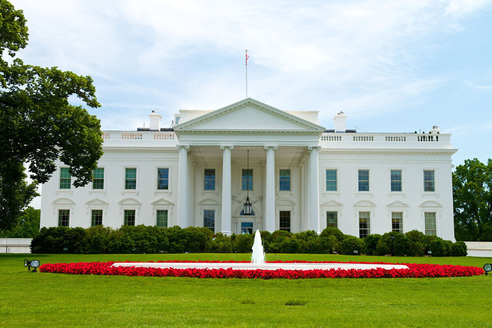 The White House with a fountain shooting water in the front surrounded by red flowers