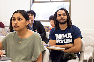 Two students seated in a classroom, listening and taking notes