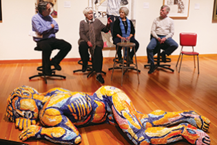 Group of four artists sit on stools talking, with large, colorful human sculpture laying on the floor in front of them