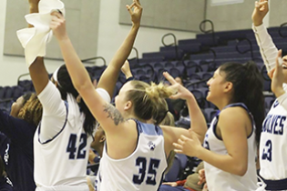 women's basketball players celebrate with arms in the air